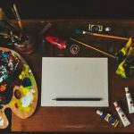 Image of paints, paint brushes, pencils, and chalks aroun a blank canvas on a desk top.