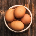 A bowl of 7 brown chicken eggs