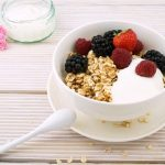 A bowl of yogurt topped with granola, blackberries, raspberries, and strawberries placed on a table with a glass of milk.